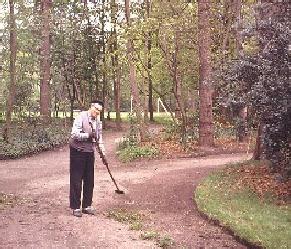 Broeder Johannes aan het werk in het bos. Op de achtergrond het voetbalveld (1968)