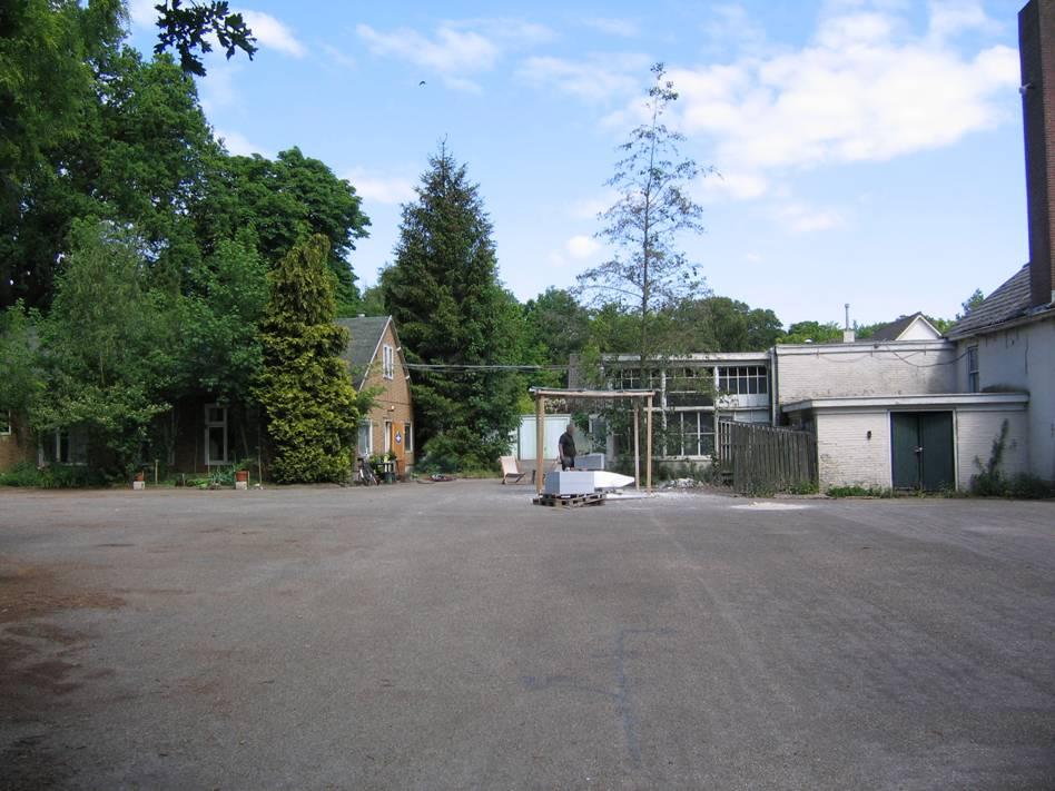 Links slaapgebouw, rechts werkplaatsen in het midden is een huidige kunstenaar-bewoner aan 't werk
