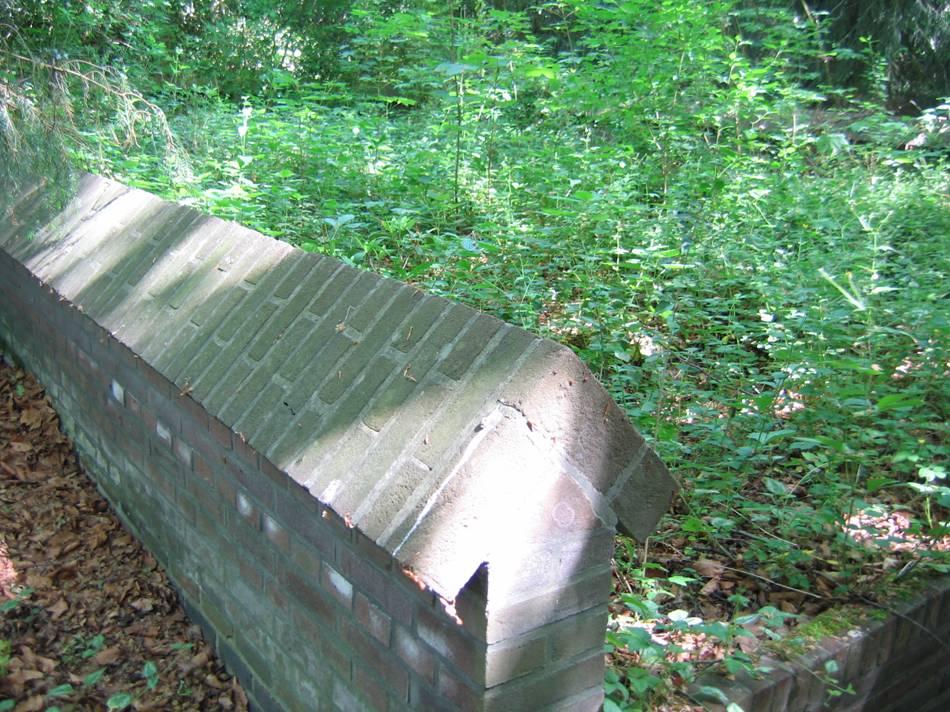 Restant muurtje van de vroegere begraafplaats