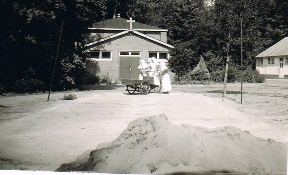 Foto van zusters met bakfiets; op de achtergrond de Kapel.